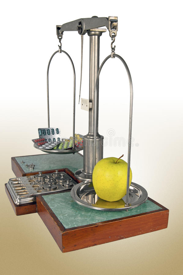 Old style pharmacy scale with yellow apple heavier than drugs. Traditional old style pharmacy scale with yellow apple heavier than drugs, small weights stock photography