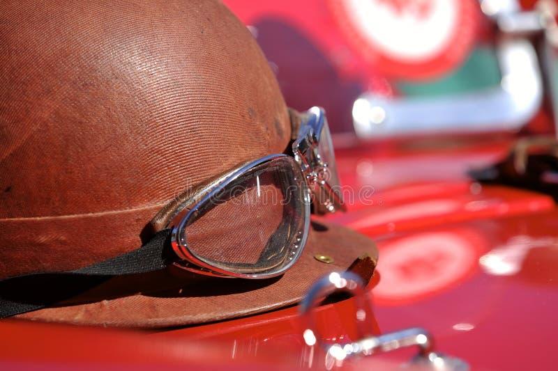 Old style race helmet on racing car stock photos