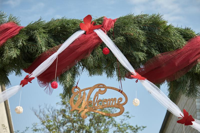 Old style rustic welcome sign on a fir tree greenery background. Copy space. Old rustic welcome sign made of wood. Word ` welcome ` decorated with colourful royalty free stock image