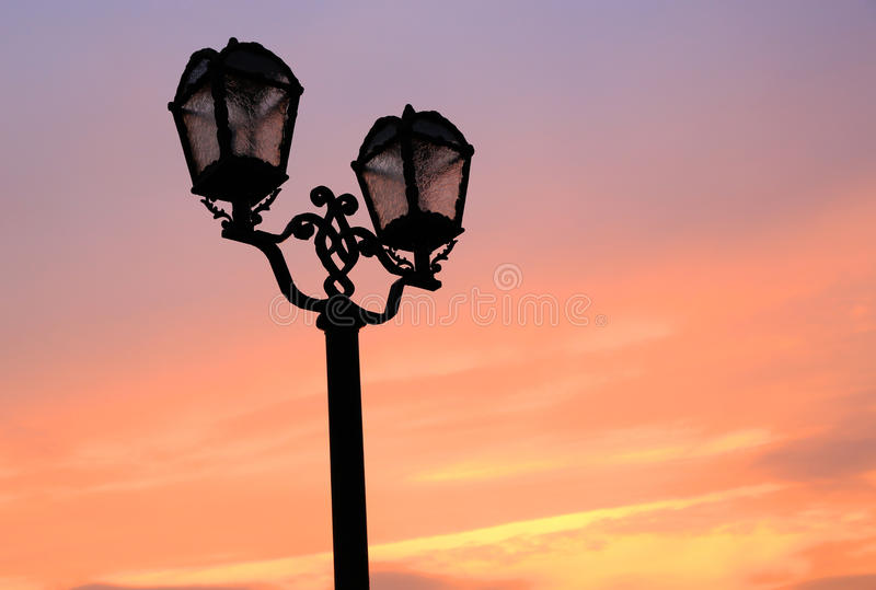 Old style street lamps on sunset sky background stock image