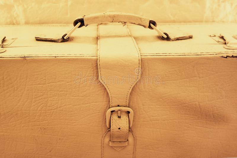 Old style vintage rustic suitcase. White painted leather bag or trunk with metal buckle strap and handle close up image. Concept royalty free stock photo