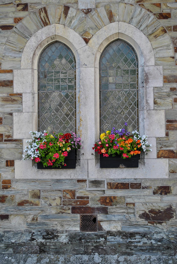 Old style windows with flower baskets royalty free stock image