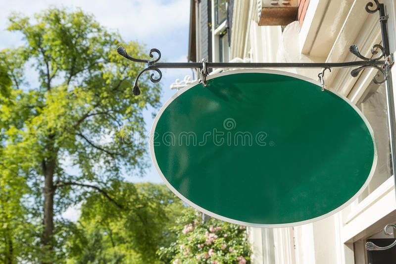 Old style wrought green iron hanging shop sign house royalty free stock photography