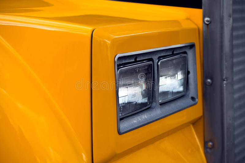 Old Style Yellow Semi Truck Head Light. Fragment of classic yellow semi truck head light stock image