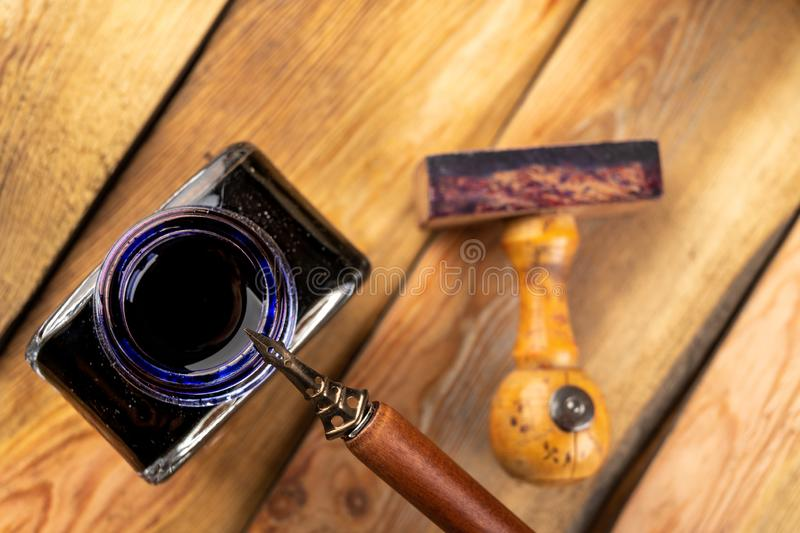 Old stylish calligraphy nib, ink and stamp on a wooden table. Writing accessories prepared for work. Dark background, antique, black, certificate, dip stock image