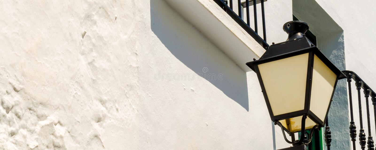 Old stylish street lamp illuminating the Spanish street, a characteristic element of traditional street architecture. Decor stock images