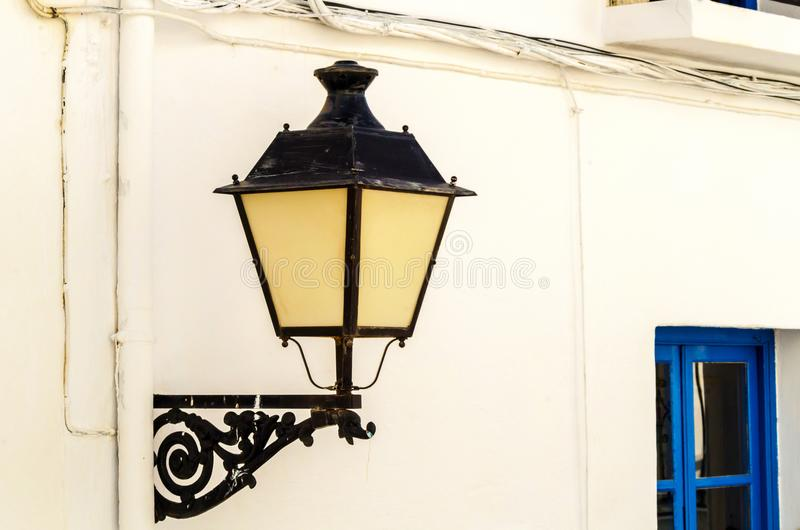 Old stylish street lamp illuminating the Spanish street, a characteristic element of traditional street architecture. Decor stock photos