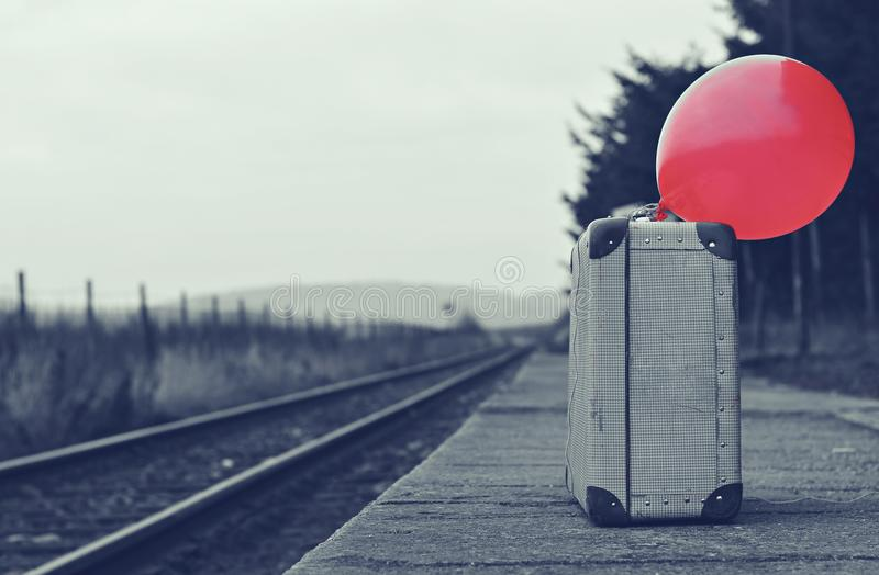 Old suitcase with a red balloon at the train station with retro effect stock photo