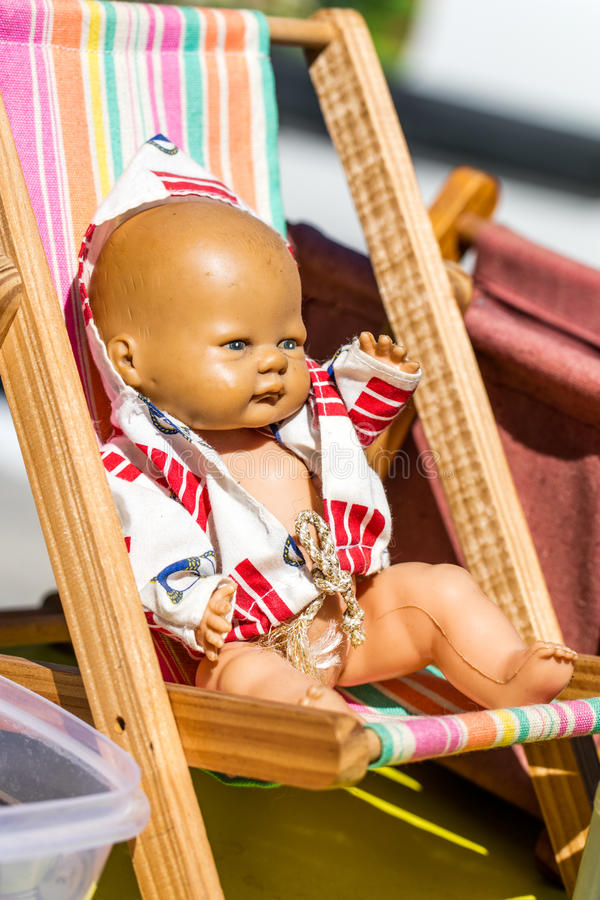 Old summer doll on a small deckchair at street fair. Display of an old summer doll on a small deckchair to recycle and reuse toys or childhood nostalgia royalty free stock photos