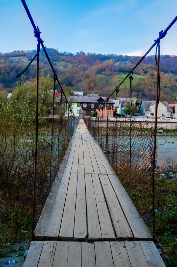 Old suspension bridge across the river in a mountain village stock images
