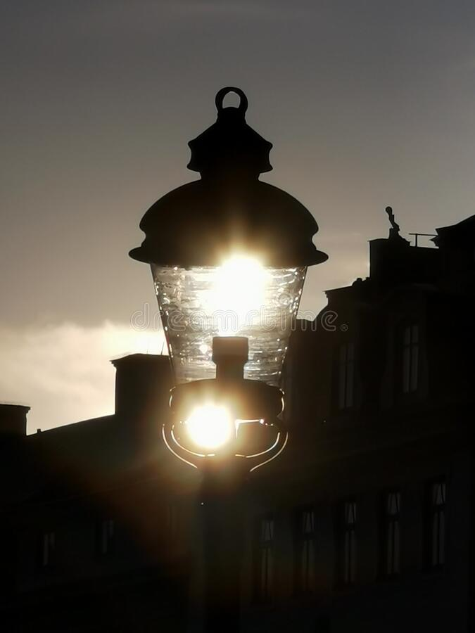 Old Swedish street lamp at Stockholm harbor flooded with sunlight stock photography