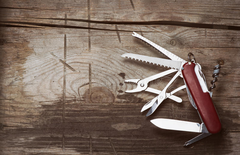 Old Swiss knife on a wooden background. Top view with copy space stock photography