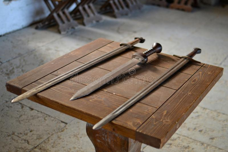 Old swords on wooden table. Old swords on a wooden table in old medieval castle in Rakvere, Estonia royalty free stock image