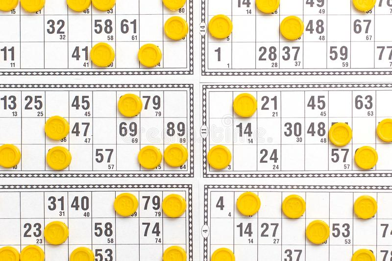 Old tabletop game lotto. Cards bingo and yellow game chips with numbers. Top view.  stock images