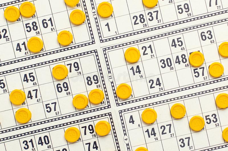 Old tabletop game lotto. Cards bingo and yellow game chips with numbers. Top view.  stock photography