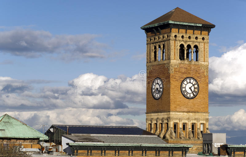 Old Tacoma City Hall Brick Building Architectural Clock Tower. Soft white clouds surround the old City Hall Building in Tacoma Washington, United States royalty free stock photography