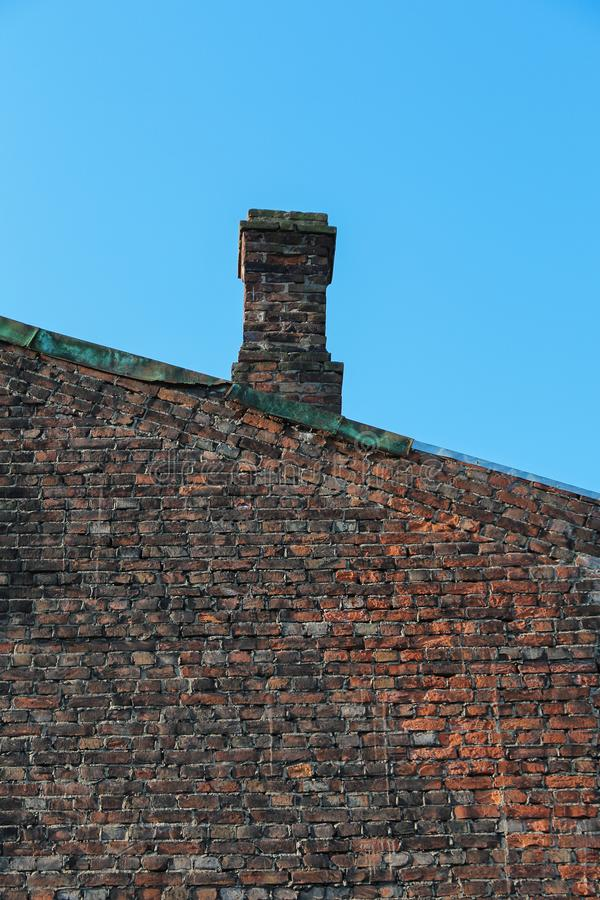 Old tall brick wall of a building with a chimney on the roof royalty free stock images