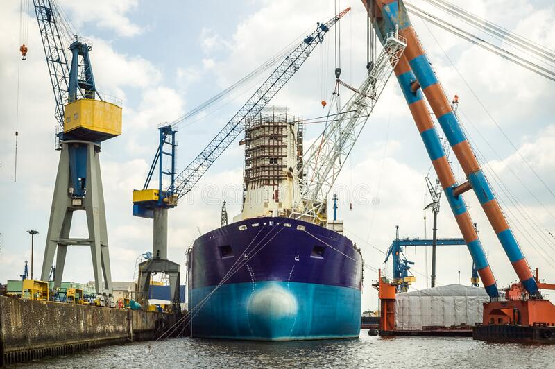 An old tanker moored in a dockyard surrounded by large lifting cranes. An old tanker moored in a dockyard, undergoing maintenance or repair, surrounded by large stock photos
