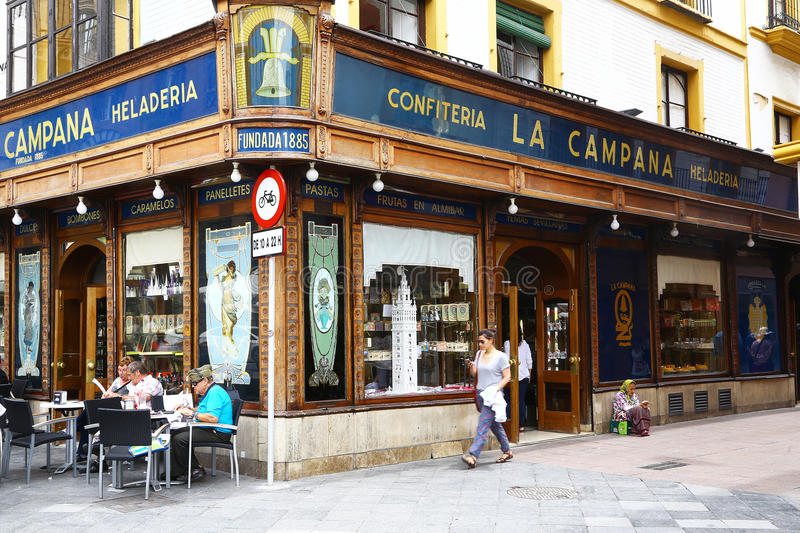Old tea room in Sevilla, Spain. Sevilla, Spain - May 27, 2014: External windows of old tea room La Campana, founded in 1885. Some people are visible at the stock photos