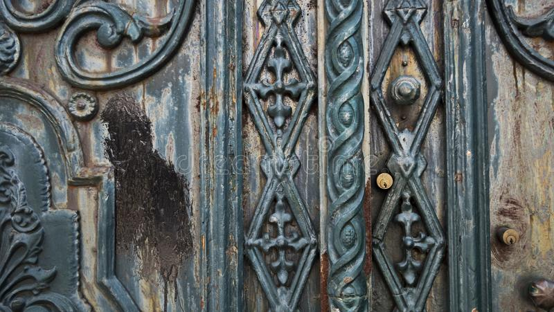 Old teal paint metal doorway. Metal doorway entrance gate with many layersof old paint and some rust.  teal blue green doornobs lock abode entrance door europe stock image