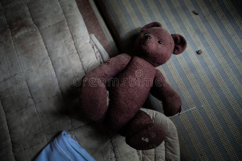 An old teddy bear lonely sadly lies on a dirty striped mattress. Poor childhood. Concept, Sentimental royalty free stock image