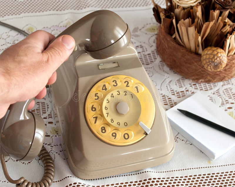 Old telephone. Vintage telephone with hands on white background stock photo