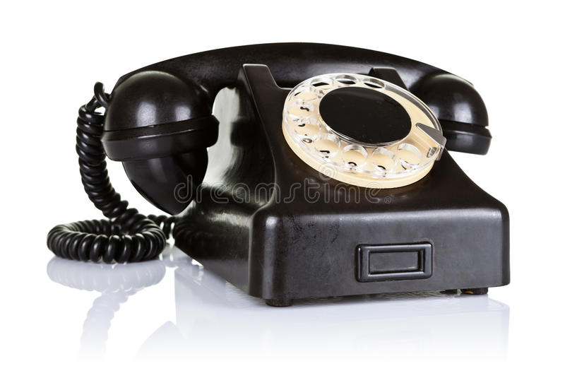 Old Telephone. Old black vintage telephone with rotary dial on white background royalty free stock image