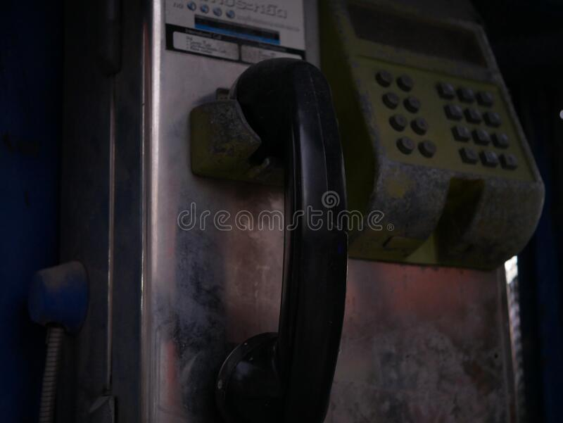 Old telephone booth close-up view. Old black public telephone booth close-up view in Thailand that never used anymore stock photo