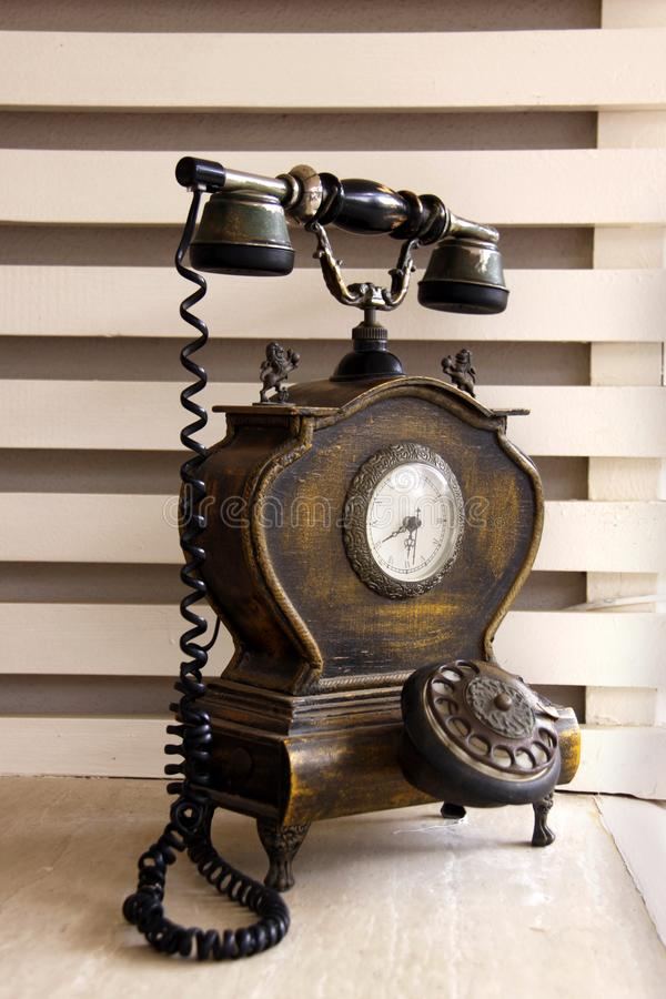 An old telephone made of wood with an analogue dialer. With a clock. Standing on a stone table royalty free stock photography