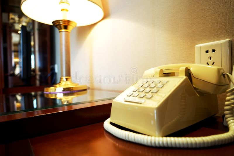 Old telephone on wooden table near wall and ramp in hotel room stock photography
