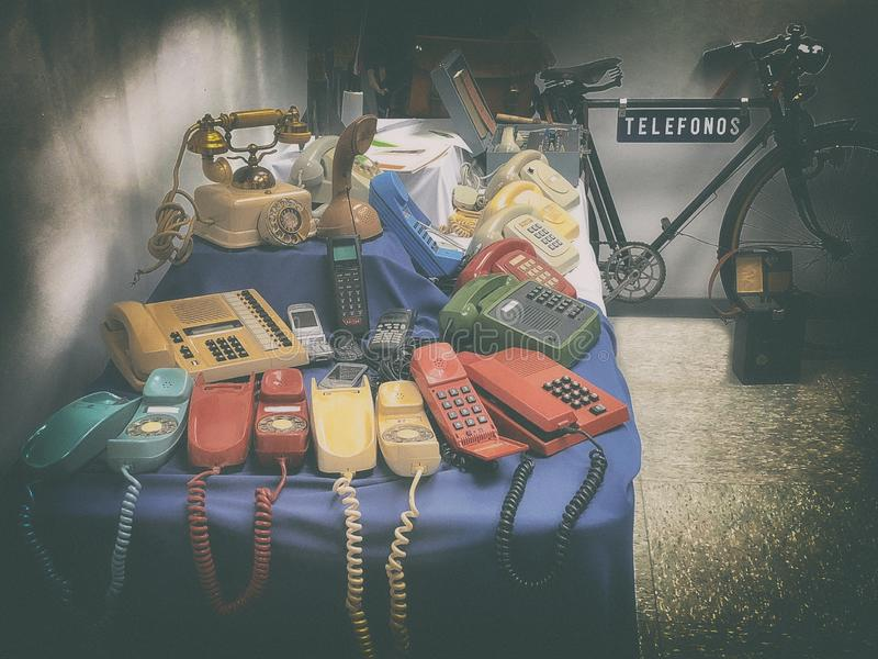 Old telephones. Of different times on a table, and telephony operator bicycle stock images