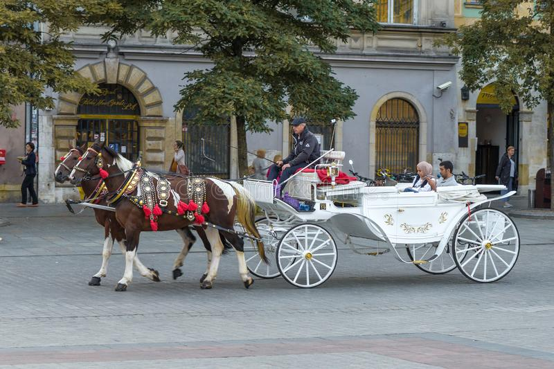 Old tenements and horse-drawn carriage in Krakow, Poland. Krakow, Poland - September 03, 2019 stock image