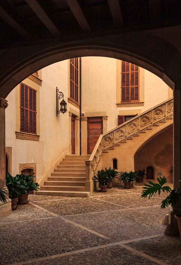 Old terracotta colored courtyard with a large staircase seen through a dark archway in a residential neighborhood in Palma stock photography
