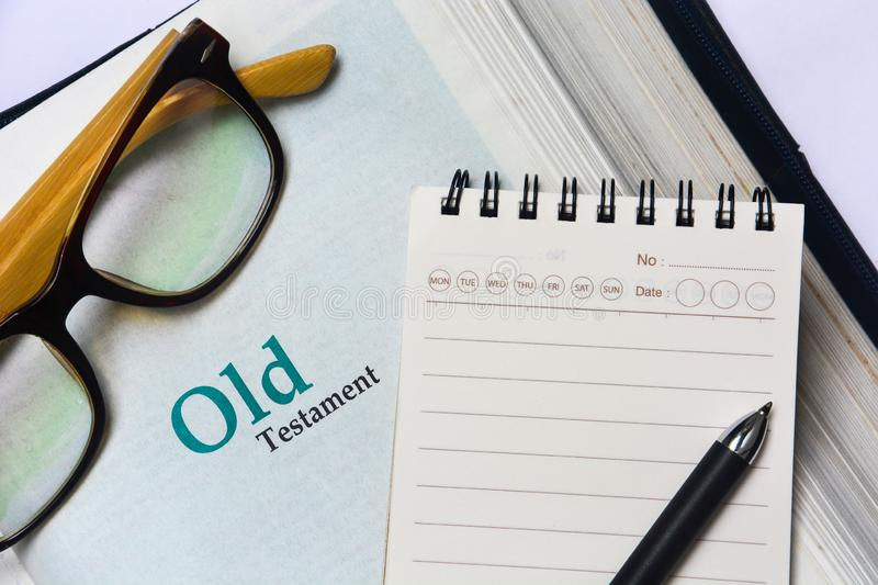Old testament cover in Holy Bible with notebook, pen and glasses. Copy space stock images