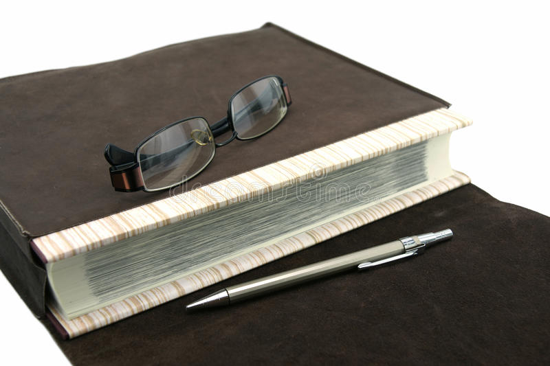 Old text book or bible with pen and eyeglasses and leather bag. An old text book or bible with pen and eyeglasses and leather bag stock photography
