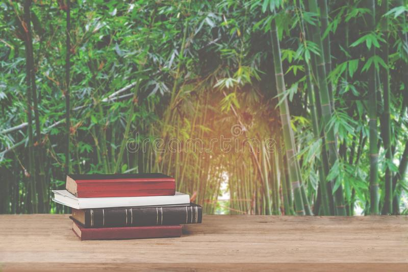Old text books on grunge wood table with bamboo stock images