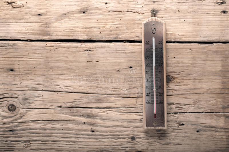 Old thermometer. On a wooden background royalty free stock photography