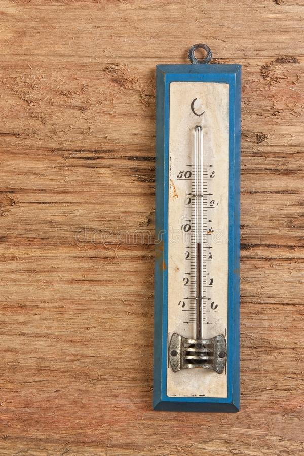 Old thermometer. On a wooden background stock images