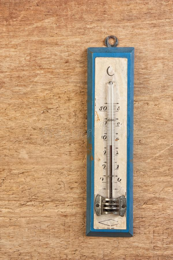 Old thermometer. On a wooden background stock image