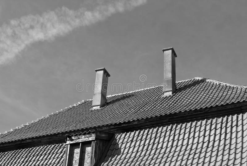 Old tiled roof with chimneys and window in black and white stock photo