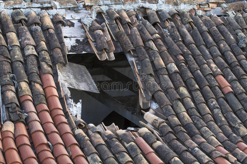 Old tiled roof with a large hole royalty free stock image