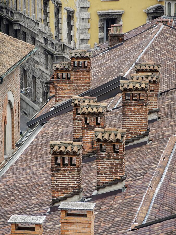 Old tiled roofs. Old tiled roofs and chimneys in the center of Milan royalty free stock photos