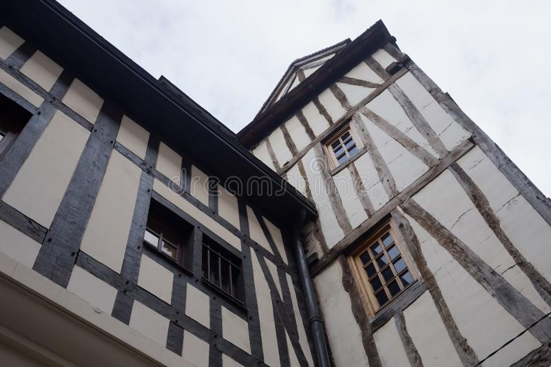 Old and tilted houses at Rue Eau de Robec in Rouen on a rainy day. Rue Eau-de-Robec is one of the main tourist streets royalty free stock images