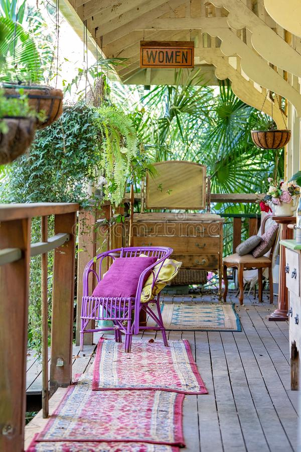 Old Timber Verandah With Vintage Furniture. An old timber verandah from yesteryear filled with vintage furniture of a bygone era stock photography
