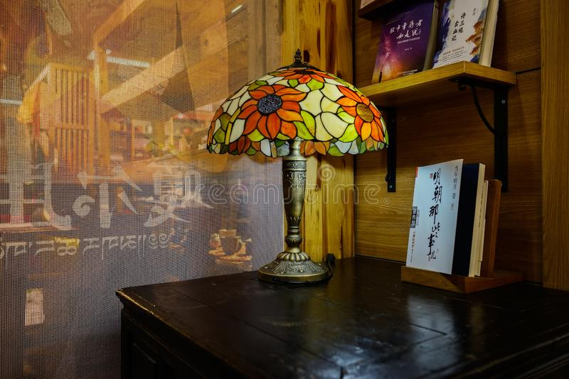 Old-time desk lamp on aged table in corner of bookstore royalty free stock photography