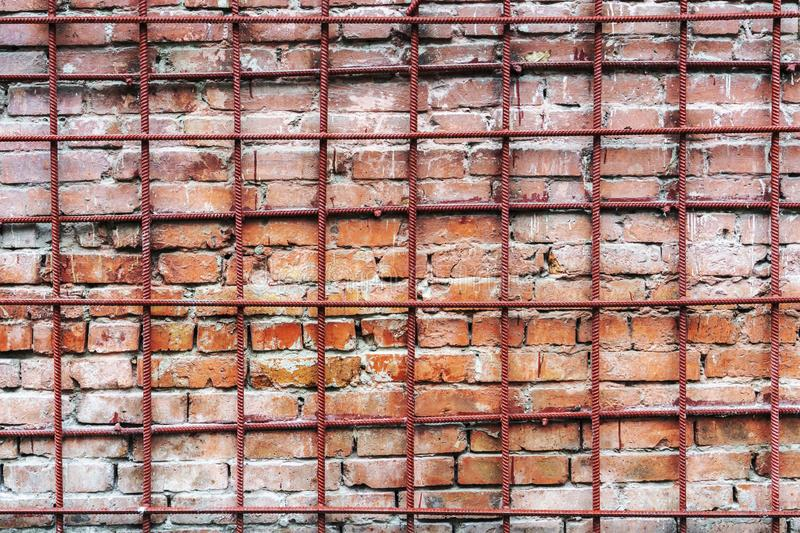 An old and time-worn red brick wall behind a metal grating.  stock image