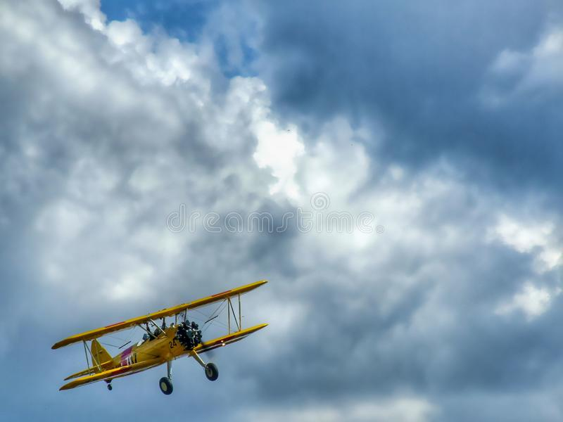 Old yellow biplane aircraft on colorful cloudy sky. stock photo