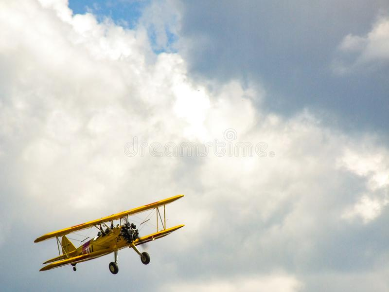 Old yellow biplane aircraft on sunny cloudy sky. royalty free stock photo