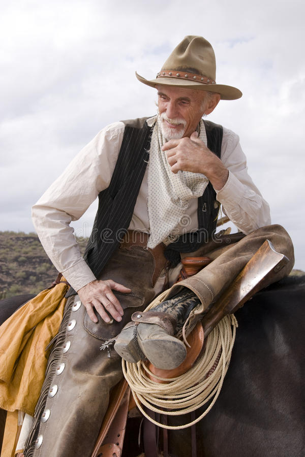 Old Timer Western Cowboy Roper. Old western cowboy rests along the trail on his horse stock photography