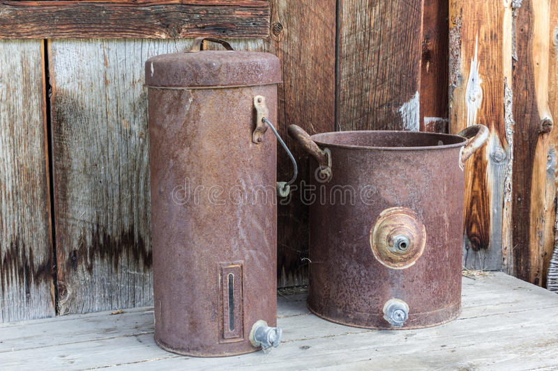 Old tin containers. Old rusted metal pail and decanter royalty free stock photography
